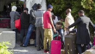 طالبي لجوء ينتظرون قبل عبورهم الحدود الامريكية الكندية بشكل غير قانوني، 6 اغسطس 2017 (GEOFF ROBINS / AFP)