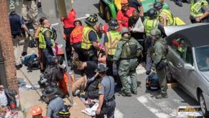 مصابون يتلقون العلاج الأولي بعد اصطدام سيارة بحشد من المتظاهرين في تشارلوتسفيل في ولاية فيرجينيا، 12 أغسطس، 2017. ( / AFP PHOTO / PAUL J. RICHARDS)