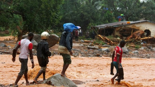 السكان يمشون عبر مياه الفيضانات بجانب مبنى متضرر في منطقة من فريتاون في 14 أغسطس / آب 2017، بعد أن هزت انهيارات أرضية عاصمة ولاية سيراليون في غرب أفريقيا. (AFP PHOTO / SAIDU BAH)