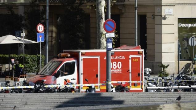 رجل شرطة يقف بجانب سيارة إسعاف بعد أن داهمت سيارة حشدا في رامبلا في برشلونة في 17 أغسطس 2017. (AFP PHOTO / Josep LAGO)