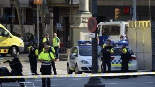 رجل شرطة وطاقم طبي بجانب سيارة إسعاف بعد أن داهمت سيارة حشدا في رامبلا في برشلونة في 17 أغسطس 2017. (AFP PHOTO / Josep LAGO)