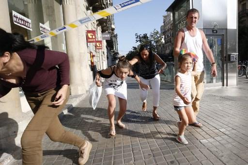يغادر الناس منطقة محاصرة بعد أن حطمت سيارة مفخخة داخل حشد، مما أسفر عن مقتل شخص واحد وإصابة اخرين بجروح في رامبلا في برشلونة في 17 أغسطس / آب 2017. (PAU BARRENA / AFP)