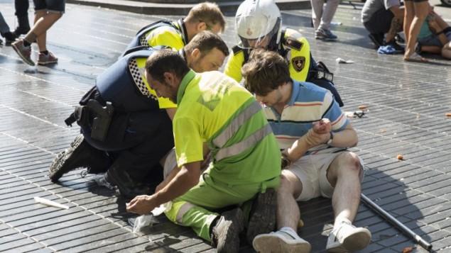 شخص يساعده عناصر شرطة اسبان ورجلان بعد هجوم دهس بشاحنة، ادى الى مقتل 13 شخصا واصابة حوالي 100 شخص في برشلونة، 17 اغسطس 2017 (AFP PHOTO / Nicolas CARVALHO OCHOA)