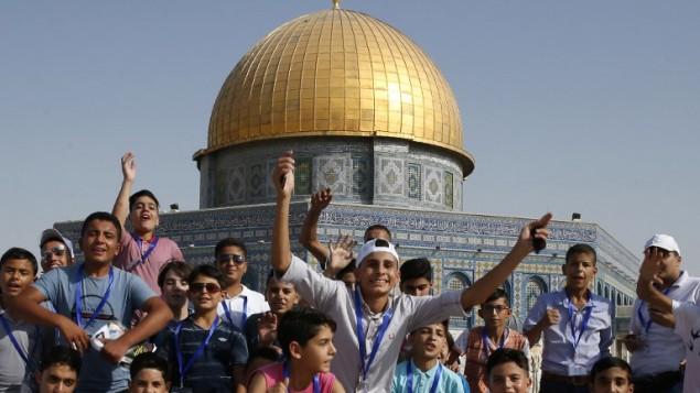 أطفال فلسطينيون من قطاع غزة في صورة مشتركة من أمام قبة الصخرة  في مجمع المسجد الأقصى في البلدة القديمة في مدينة القدس، 20 أغسطس، 2017، خلال زيارة يقومون بها إلى المدينة للمرة الأولى في إطار برنامج تبادل تنظمه وكالة الأمم المتحدة لغوث وتشغيل اللاجئين الفلسطينيين.  (AFP PHOTO / AHMAD GHARABLI)