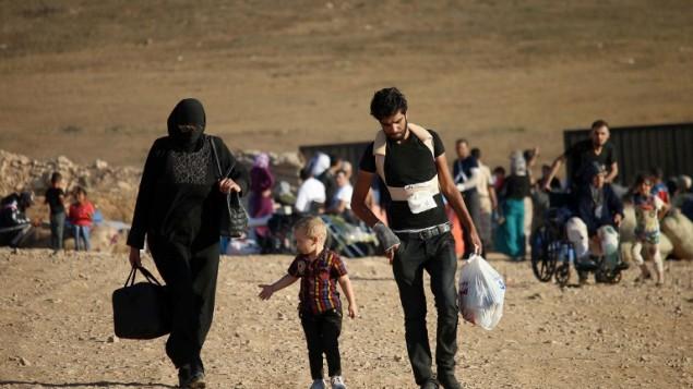 سوريون يسيرون وهم يحملون أمتعتهم في 22 أغسطس، 2017 بعد اجتياز الحدود السورية-الأردنية بالقرب من بلدة نصيب مع عودتهم إلى منازلهم في أعقاب اتفاق وقف إطلاق النار الأمريكي-الروسي الذي تم التوصل إليه في في وقت سابق من العام في محافظات درعا والقنيطرة والسويداء في جنوب سوريا. (AFP/Mohamad ABAZEED)