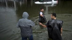 اشخاص يمشون خلال الفيضانات في شوارع هيوستن، تكساس في اعقاب الاعصار هارفي، 27 اغسطس 2017 (AFP PHOTO / Brendan Smialowski)