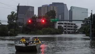طواقم الإنقاذ تبحث عن أشخاص بحاجة إلى الإنقاذ بعد أن تسبب الإعصار 'هارفي' بفيضانات كارثية في مدينة هيوستن في ولاية تكساس الأمريكية، 27 أغسطس، 2017.   (AFP PHOTO / MARK RALSTON)