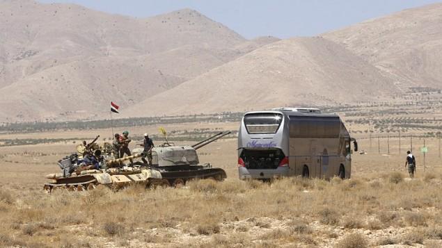 دبابة تابعة لقوات النظام السوري تراقب حافلة سوف تنقل مقاتلي تنظيم الدولة الإسلامية من قارة السورية الى منطقة دير الزور، 28 اغسطس 2017 (LOUAI BESHARA / AFP)
