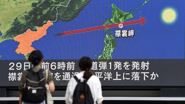 اشخاص امام شاشة كبيرة تظهر مسار الصاروخ الكوري الشمالي الذي مر فوق اليابان، في طوكيو، 29 اغسطس 2017 (AFP PHOTO / Toshifumi KITAMURA)
