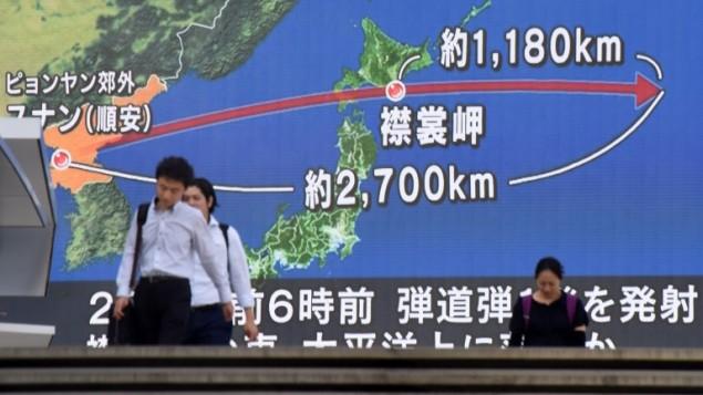 اشخاص امام شاشة كبيرة تظهر مسار الصاروخ الكوري الشمالي الذي مر فوق اليابان، في طوكيو، 29 اغسطس 2017 (KAZUHIRO NOGI / AFP)