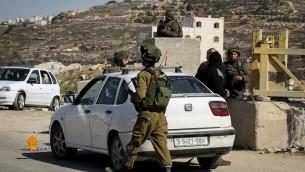 صورة توضيحية: جنود اسرائيليون يفتشون سيارات فلسطينية في حاجز في بلدة يطا بالضفة الغربية، 10 فبراير 2017 (Wisam Hashlamoun/Flash90)