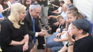 رئيس الوراء بنيامين نتنياهو وزوجته سارة يعزيان اقرباء ثلاثة ضحايا هجوم مستوطنة حلميش في الضفة الغربية، 22 يوليو 2017 (Amos Ben Gershom/GPO)