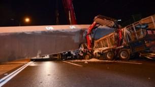عمال الإنقاذ والشرطة في موقع انهيار جسر مشاة على شاحنة في الطريق السريع رقم 4 بالقرب من غيفعات شموئيل، 14 أغسطس، 2017. (Moti arelitz/Flash90)