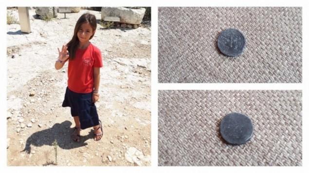 الطفلة هاليل يافيه (8 أعوام) تحمل عملة نقدية نادرة بقيمة نصف شيكل يعود تاريخها إلى 2,000 عاما كانت عثرت عليها، 23 أغسطس، 2017 في حلميش. (courtesy)