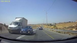 تحاول السيارة  الزرقاء تجاوز الشاحنة البيضاء من خلال الاندماج فى المسار المعاكس، حيث تصطدم تقريبا بالسيارة القريبة على الطريق رقم 60 فى الضفة الغربية. (Courtesy: Avraham Binyamin)
