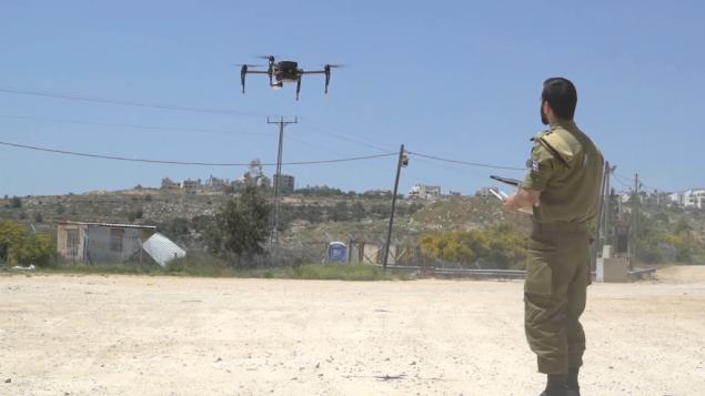 جندي إسرائيلي من سلاح جمع المعلومات الميدانية يقوم بتشغيل طائرة مسيرة جديدة قام الجيش بشرائها لقادة السري.(Screen capture: IDF Spokesperson's Unit)