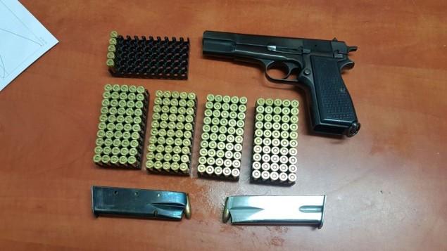 مسدس ومخزني مسدس و200 طلقة ذخيرة تمت مصادرتها في مداهمة لمنزل عائلة في مدينة الخليل في الضفة الغربية، 2 أغسطس، 2017. (الشرطة الإسرائيلية)
