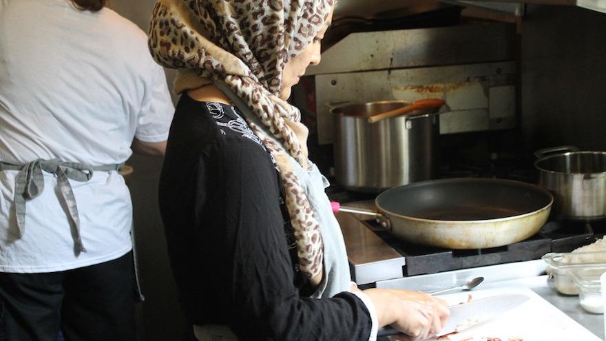 نسيمة، لاجئة من أفغانستان التي لم تعط اسمها عائلتها، تقطع الفطر لطهي الشكشوكة، 11 أغسطس 2017. (Ben Sales/JTA)