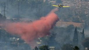 صورة توضيحية: طائرة اطفاء تسكب مواد اخماد نيران خلال حريق في ضواحي القدس (Nati Shohat/Flash90)