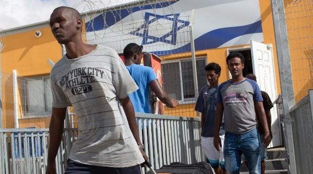 مهاجرون افارقة يحملون ممتلاكتهم بعد خروجهن من مركز الاحتجاز حولوت في صحراء النقب، 25 اغسطس 2015 (AFP PHOTO/MENAHEM KAHANA)