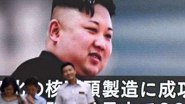صورة لاشخاص يمرون امام شاشة في طوكيو تعرض صورة للقائد الكوري الشمالي كيم جون أون، في 9 اغسطس 2017 (AFP PHOTO / Kazuhiro NOGI)