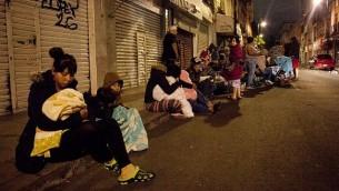 اشخاص يتجمعون في شوارع العاصمة مكسيكو بعد زلزال بقوة 8 درجات، 7 سبتمبر 2017 (Pedro Pardo/AFP)