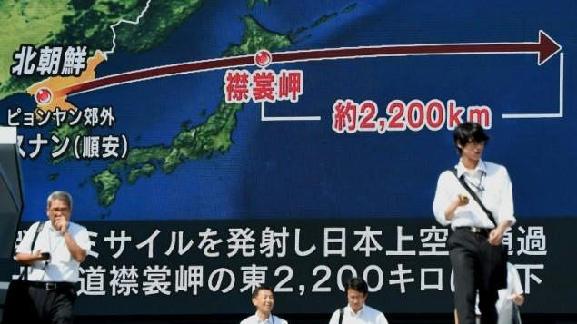 اشخاص امام شاشة كبيرة تظهر مسار الصاروخ الكوري الشمالي الذي مر فوق اليابان، في طوكيو،15 سبتمبر 2017 (AFP PHOTO / Toru YAMANAKA)