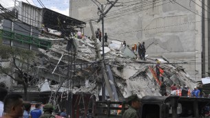 عمال الانقاذ فوق حطام مبنى انهار في زلزال في المكسيك، 19 سبتمبر 2017 (OMAR TORRES / AFP)