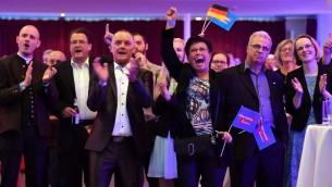 مؤيدون لحزب 'البديل من أجل ألمانيا' يحتفلون بعد بث نتائج استطلاع الرأي على التلفزيون العام في تحمع بمناسبة ليلة الإنتخابات في مدينة إرفورت شرقي ألمانيا، خلال يوم الإنتخابات التشريعية في 24 سبتمبر، 2017. (. / AFP PHOTO / dpa / Martin Schutt / Germany OUT)