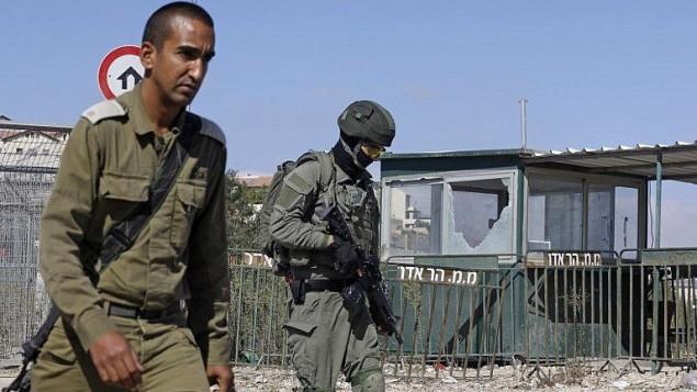 عناصر امن اسرائيليون يمشون امام بوابة مستوطنة هار ادار في الضفة الغربية بعد هجوم قُتل فيه ثلاثة عناصر امن، 26 سبتمبر 2017 (Menahem Kahana/AFP PHOTO)