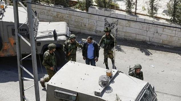 صورة تم التقاطها في 26 سبتمبر، 2017، في قرية بيت سوريك في الضفة الغربية تظهر جنودا إسرائيليين يقومون باعتقال فلسطيني، أشارت تقارير إلى أن شقيقه قام بارتكاب هجوم أسفر عن مقتل ثلاثة إسرائيليين في مستوطنة هار أدار. (AFP PHOTO / ABBAS MOMANI)