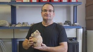 البروفيسور في جامعة حيفا داني روزنبرغ يحمل صوامع الحبوب الطينية التي يبلغ عمرها 7،200 سنة والتي وجدت في تل تساف في غور الأردن. (Haifa University)
