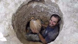 يعمل ديفيد تنعامي، عالم آثار في سلطة الآثار الإسرائيلية، يجد طريقه إلى فتح القبر الضيق لإحضار جرة في موقع دفن كنعاني بالقرب من حديقة الحيوانات التوراتية في القدس. (Shua Kisilevitz, Israel Antiquities Authority)