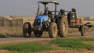 مزارع يعود من العمل في الدفيئة في كيبوتس ناحال عوز، بالقرب من الحدود بين إسرائيل وغزة.  (Tsafrir Abayov/Flash90)