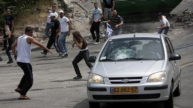متظاهرون يلقون بالحجارة على مركبة في حي سلون في القدس في عام 2011. (Yonatan Sindel / Flash90)