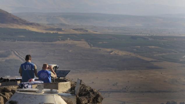 عناصر قوات حفظ السلام للأمم المتحدة يراقبون الطرف السوري من مرتفعات الجولان، يوليو 2012 (Tsafrir Abayov/Flash90)