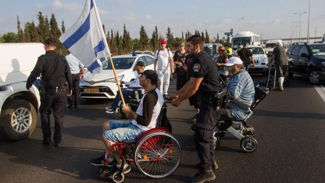 صورة توضيحية، متظاهرين ذوي اعاقات خلال مظاهرة في الشراع الرئيسي امام كيبوتس يكوم في مركز اسرائيل، 14 اغسطس 2017 (Flash90)