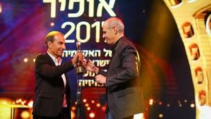 ساسون غاباي، يسار، يسلم جائزة أفضل مخرج لشمويل ماعوز في حفل جوائز أوفير 2017 في 19 سبتمبر 2017. (Flash90)