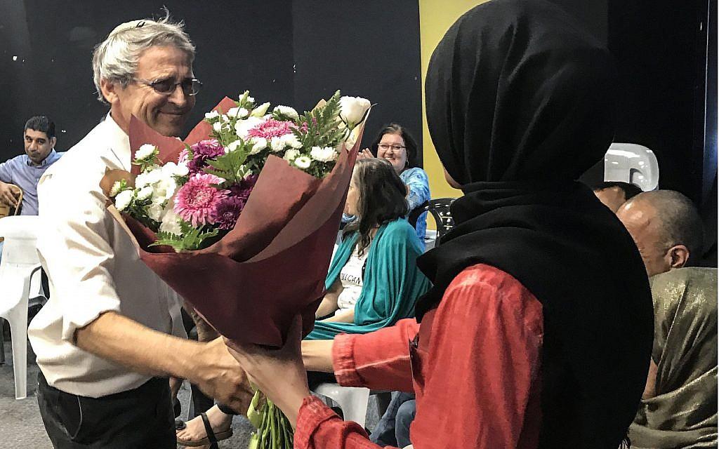 مؤسس منظمة 'تاغ مئير' غادي غفرياهو يهدي باقة زهور لميرفت إغبارية، طالبة جامعية اعتقد أحد الركاب عن طريق الخطأ على متن حافلة إلى بئر السبع إنها تعتزم تنفيذ هجوم. (Gabriel Carrol/Times of Israel)