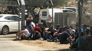 عمال فلسطينيون يجلسون في مستوطنة هار أدار بعد إخراجهم من المنطقة من قبل الجنود في أعقاب هجو وقع عند مدخل المستوطنة في 26 سبتمبر، 2017. (Jacob Magid/Times of Israel)