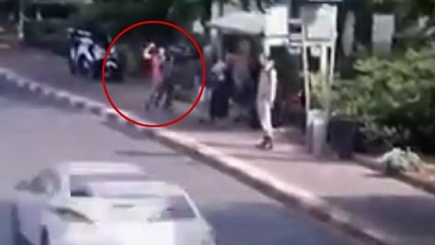 صورة من مقطع فيديو يظهر منفذ هجوم الطعن (في الدائرة) خالد بسطي يقوم بطعن إسرائيليين خلال وقوفهم في محطة للحافلات في شارع 'القدس' في مدينة رعنانا في 12 أكتوبر، 2015. (لقطة شاشة)