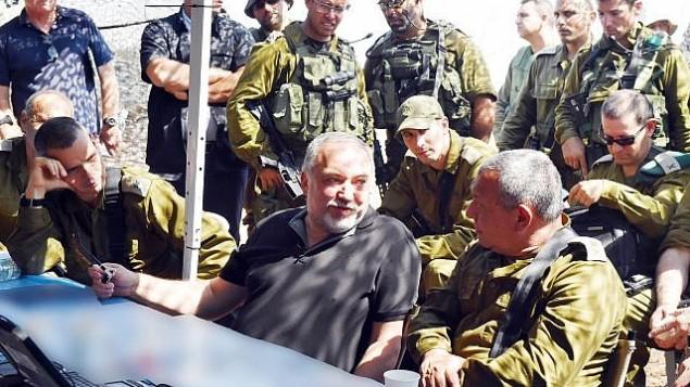 وزير الدفاع أفيغدور ليبرمان، في الوسط، يتحدث مع رئيس هيئة أركان الجيش الإسرائيلي غادي آيزنكوت، من اليمين، وإلى جانبه، من اليمين، يجلس قائدة المنطقة الشمالية في الجبش الإسرائيلي الميجر جنرال يوئيل ستريك، خلال زيارة لتمرين كبير يجريه الجيش الإسرائيلي في شمال إسرائيل، 12 سبتمبر، 2017. (Ariel Hermoni/Defense Ministry)