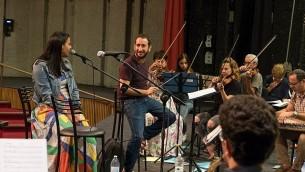 """قائد أوركسترا القدس الشرقية الغربية، توم كوهين، والمغنية نسرين قادري، في تمرين لحفل """"كلّنا"""" في القدس. (Gil Rouvio/Mekudeshet)"""