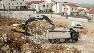 عمال فلسطينيون يعملون في موقع بناء مشروع سكني جديد في مستوطنة أريئيل القريبة من مدينة نابلس في الضفة الغربية، 25 يناير، 2017. (AFP Photo/Jack Guez)