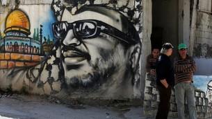 يقف لاجئون فلسطينيون بجانب كتابات تحمل صورة لرئيس السلطة الفلسطينية الراحل ياسر عرفات في مخيم عين الحلوة للاجئين بالقرب من مدينة صيدا بجنوب لبنان في 16 مارس / آذار 2015. (AFP/Joseph Eid)