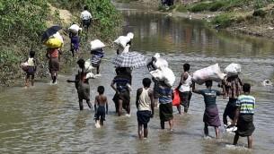 لاجئون من أبناء الروهينغا يحملون إمدادات عبر مخيم جالباتولي في 'الأرض المحرمة' بين ميانمار وبنغلاديش، في منطقة غومدوم، 16 سبتمبر، 2017. (AFP Photo/Dominique Faget)