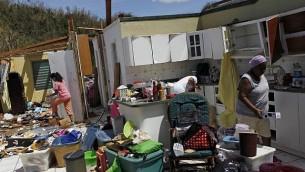 يجمع أفراد اائلة ممتلكاتهم بعد أن دمرت رياح الإعصار منازلهم في توا باجا، غرب سان خوان، بورتوريكو، في 24 سبتمبر 2017 بعد مرور إعصار ماريا. (AFP PHOTO / Ricardo ARDUENGO)