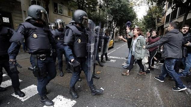 متظاهرون يواجهون عناصر الشرطة الاسبانية بعد مصادرة صناديق الاقتراع في برشلونة في يوم الاستفتاء حول استقلال كتالونيا، 1 اكتوبر 2017 (AFP PHOTO / PAU BARRENA)