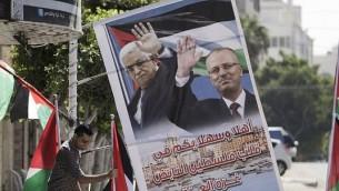 صاحب متجر فلسطيني يعرض أعلاما فلسطينية وملصق يحمل صورة رئيس الوزراء الفلسطيني راي الحمد الله ورئيس السلطة الفلسطينية محمود عباس، 1 أكتوبر، 2017، في مدينة غزة. (AFP PHOTO/MAHMUD HAMS)