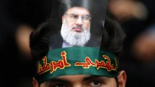 مؤيد لمنظمة 'حزب الله' يضع على رأسه صورة للأمين العام للمنظمة حسن نصر الله خلال إحياء  'يوم عاشوراء' في الضاحية الجنوبية للعاصمة اللبنانية بيروت، 1 أكتوبر، 2017. ( AFP PHOTO / ANWAR AMRO)